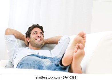 Smiling young man relaxing and dreaming on sofa at home