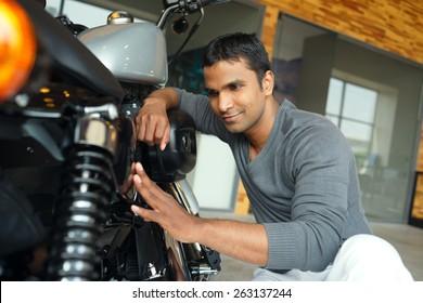 Smiling young man repairing his motorcycle