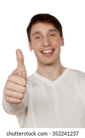 smiling young man showing thumbs up