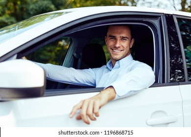 Smiling young man sitting in his car