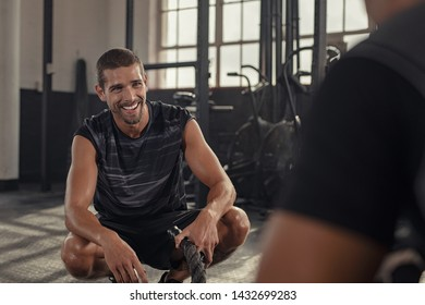 Smiling young man sitting on his toes taking a break after doing fitness workout while talking with his personal trainer. Happy sweaty man resting after battle ropes exercise at gym.