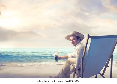 Smiling young man sitting on a deckchair and holding a cocktail at the seaside