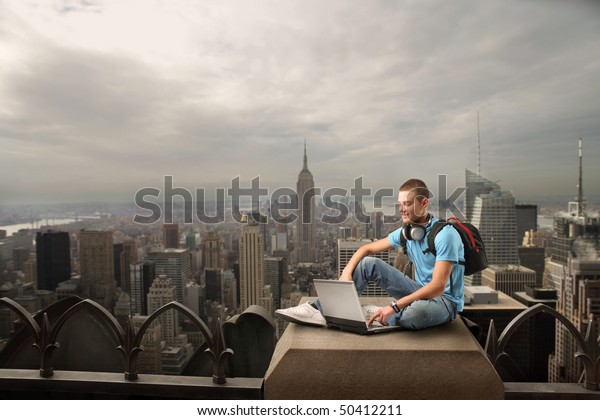 Smiling young man sitting on the top of a skyscraper and using a laptop