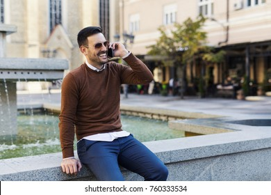Smiling young man sitting and speaking on the phone