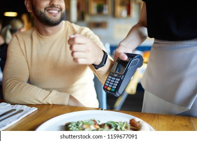Smiling young man with smartwatch keeping his wrist close to payment machine while using transfer system to pay for meal
