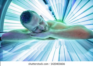 Smiling young man in solarium relaxing while lying on stomach and enjoying