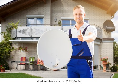 Smiling Young Man Standing Outside The House Holding Satellite Dish Showing Thumb Up Sign
