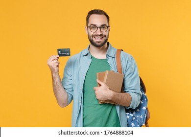 Smiling young man student in casual clothes glasses backpack hold books isolated on yellow background. Education in high school university college concept. Mock up copy space. Hold credit bank card