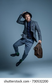 Smiling young man in suit and hat jumping up with leather bag in his hand