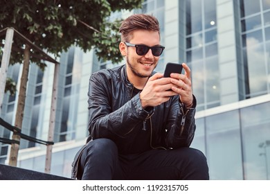 Smiling young man in sunglasses with stylish hair dressed in black leather jacket using smartphone while sitting near a skyscraper.