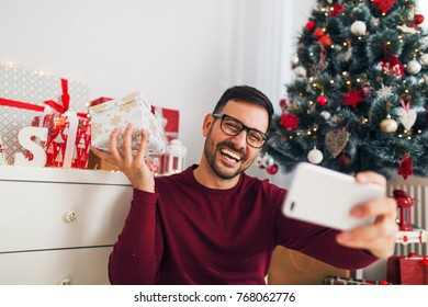 Smiling young man taking photo with Christmas gifts and decoration
