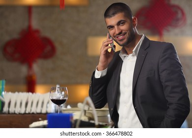 Smiling young man talking on the phone while drinking wine at the bar