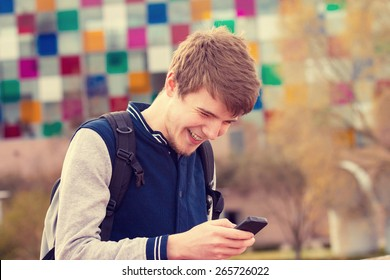 Smiling young man taping on mobile phone in a city .Young smiling student  outdoors talking on cell smart phone.Life style.City