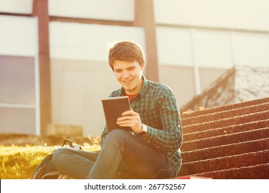 Smiling young man taping on tablet in a city on stair .Young smiling student  outdoors  with tablet.Life style.City