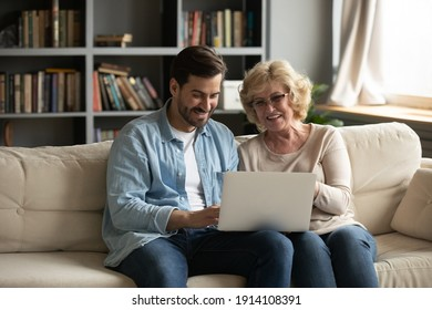 Smiling young man teaching elderly senior mother in eyeglasses using computer applications, showing new software at home. Happy two generations family enjoying watching funny movie on laptop online.