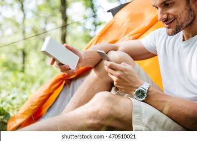 Smiling young man tourist using mobile phone and portable mini speaker in forest