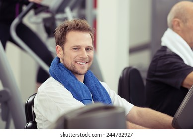 Smiling young man training at the gym working out on the equipment with a towel around his neck, in a health and fitness concept