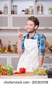 Smiling young man trying to cook dinner in kitchen