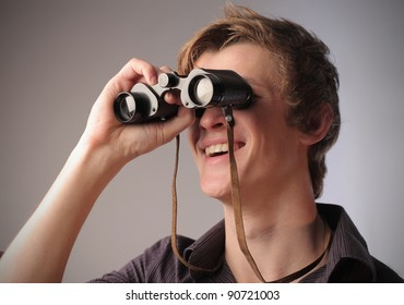 Smiling young man using binoculars