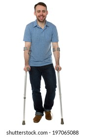 Smiling young man using crutches keeping a positive attitude in spite of his injury or handicap, full length on white