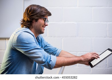Smiling young man using digital tablet in creative office