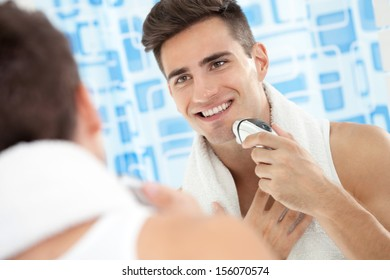 Smiling young man using electric shaver front of mirror