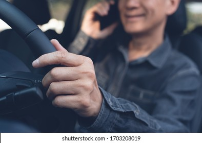 Smiling young man using mobile smart phone calling while driving a car, Driver talking via smartphone inside a car, close up. Transportation, people lifestyle concept
