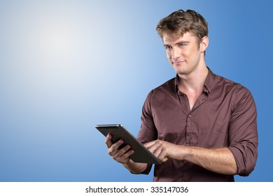 Smiling young man using tablet computer