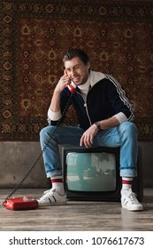 smiling young man in vintage clothes sitting on retro tv set and talking by phone in front of rug hanging on wall