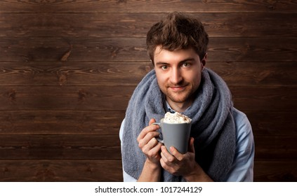 Smiling young man in warm clothing with cup of hot coffee or hot choclate. Coffee lover.