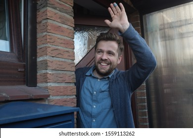 Smiling young man waving with a friendly cheerful smile to his new neighbours.