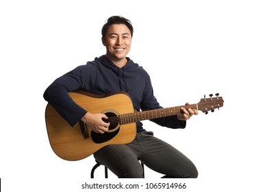 Smiling young man wearing a blue hoodie strumming on a acoustic guitar. Sitting down in front of a white background.