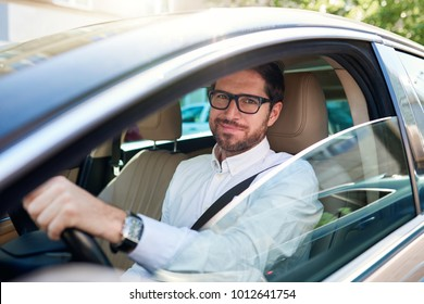 Smiling young man wearing glasses sitting behind the wheel of his car driving through the city