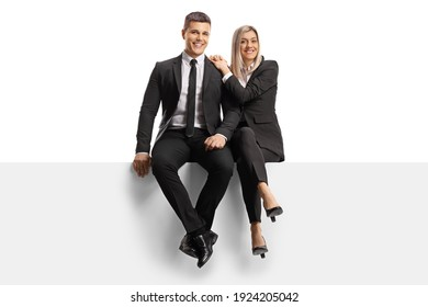 Smiling young man and woman in business clothes sitting on a blank panel isolated on white background