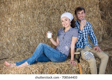 smiling young man and woman chatting and enjoying fresh milk in the hay