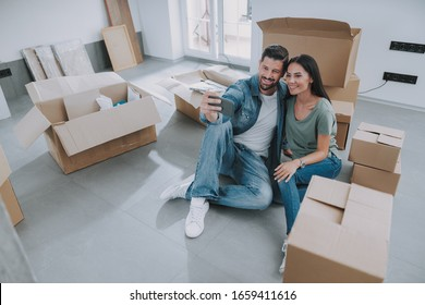 Smiling young man and woman holding smartphone ans sitting near boxes