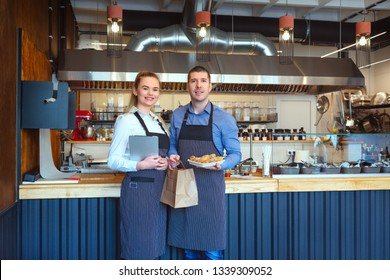 Smiling young man and woman using tablet at small eatery restaurant – Happy business owners in apron holding paper bag with to go order from online customers