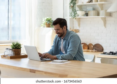 Smiling young man working on laptop in modern kitchen, checking email in morning, writing message in social network, happy young male using internet banking service, searching information