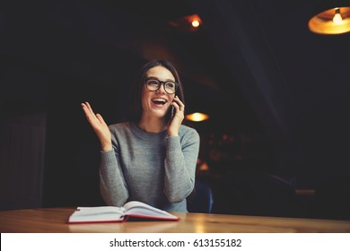 Smiling young manager talking with colleague on mobile phone and sharing exciting story after reading book in cafe. Positive hipster girl telling latest news to friend via smartphone. Copy space area