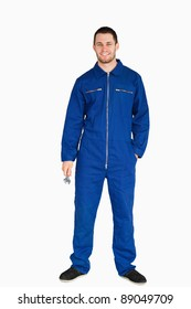 Smiling young mechanic in boiler suit holding a wrench against a white background