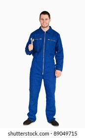 Smiling young mechanic in boiler suit with a wrench against a white background