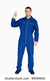 Smiling young mechanic in boiler suit pointing up against a white background