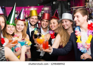 Smiling young men and women celebrating birthday in the bar at evening