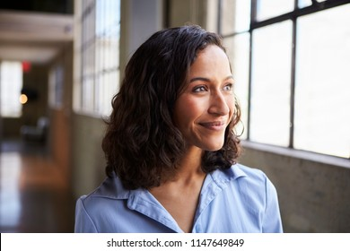 Smiling young mixed race businesswoman looking away