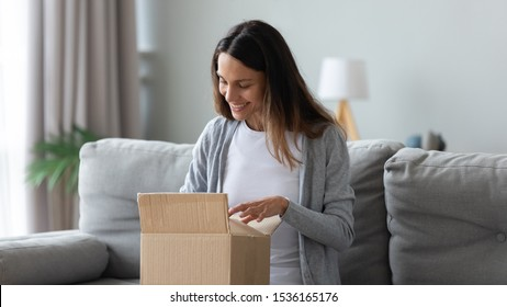 Smiling young mixed race female customer unpacking carton box, looking inside, happy get wished item order from internet store. Positive client satisfied with trusted company fast shipment delivery.