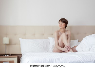 Smiling young model posing naked on hotel's bed