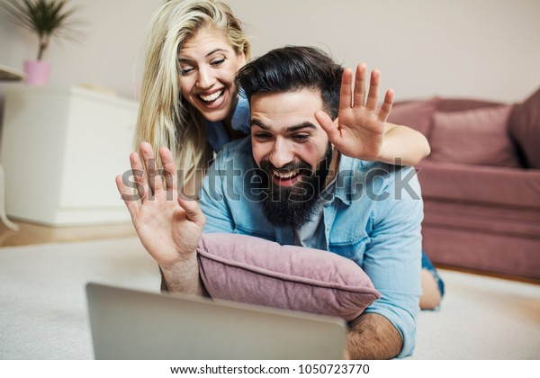 Smiling young modern couple having video call