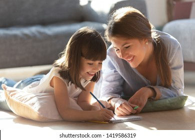 Smiling young mom and cute little daughter lying on warm floor at home drawing in album together, happy parent or nanny have fun spending time painting with colorful pencils with preschooler kid