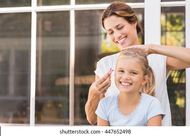 Smiling young mom making the hair tail to her daughter. Cheerful mother applying clips to daughter hair. Portrait happy woman and little girl laughing together in a summer day.