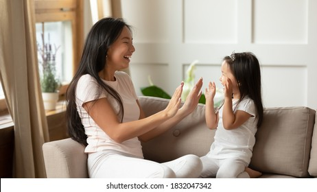 Smiling young mother and adorable little daughter wearing princess diadem clapping hands, sitting on couch, loving mum and cute toddler child girl having fun together, enjoying leisure time